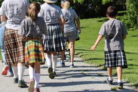 A group of kids walk down a street in kilts